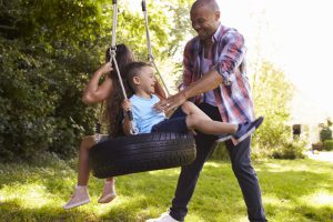 father with kids on tire swing